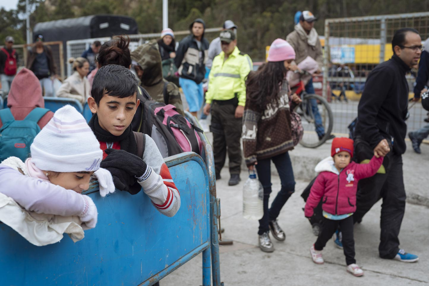 Jesús Skinner (12) y Camila Skinner (10) conversan mientras esperan junto a su madre su turno en la fila preferencial para sellar sus pasaportes en la Aduana de Ecuador, y luego seguir su viaje hacia Lima, Perú.